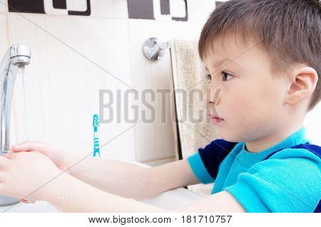 Boy washing hands child personal health care hygiene concept kid washing hand in wash basin in bathroom healthy lifestyle
