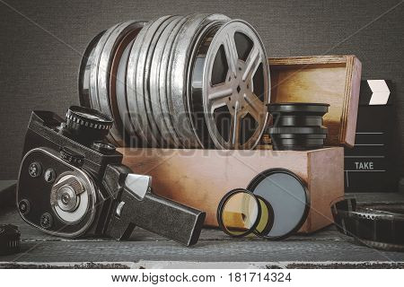 Reels with films in a wooden box lens clapperboard and an old movie camera are on the table