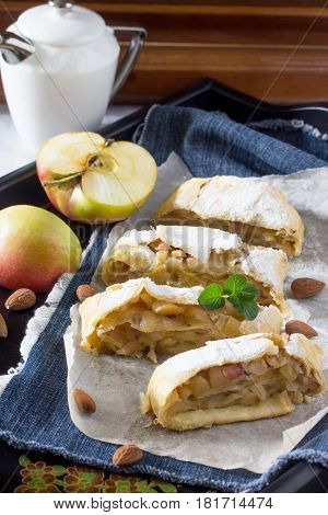 Tea And Sliced Homemade Apple Strudel With Fresh Apples, Nuts And Powdered Sugar On A Vintage Wooden