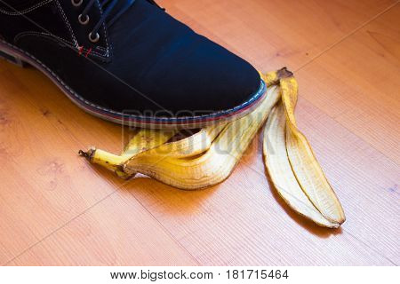 Blue shoe of young man slipped on a banana peel.