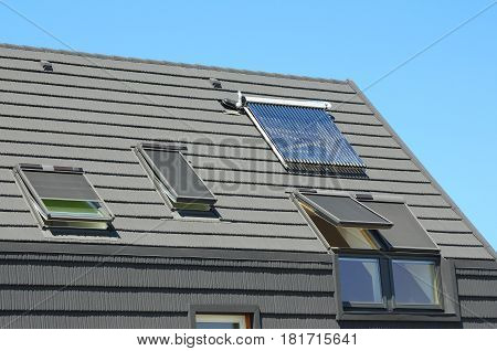 Attic skylight. Modern House Roof with Solar Water Heater Solar Panels and Skylights Beautiful New Contemporary House with Solar Panels. Open attic skylights.