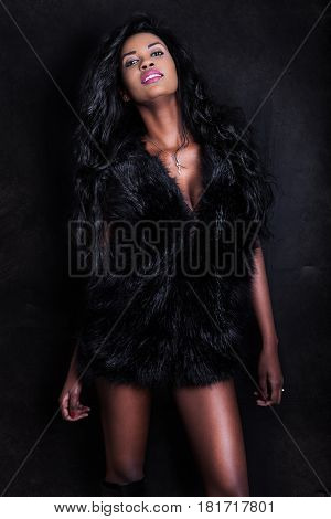 Beautiful young African American seductive black model woman on dark background. An attractive young woman wearing a furry black vest. Sensual look and perfect physique.