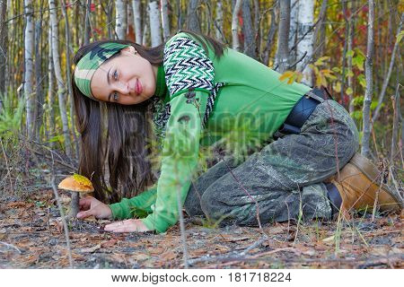 Beautiful girl with a mushroom found in the taiga
