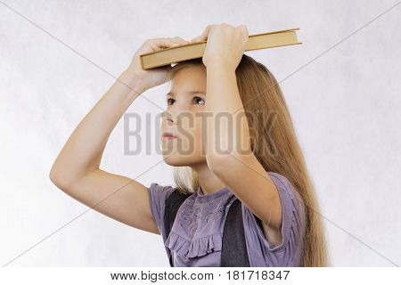 The girl does not want to read an uninteresting book textbook