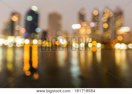 City office building blurred bokeh light at night with water reflection abstract background