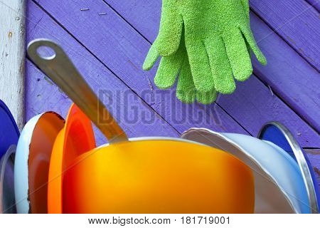 Green gloves against violet boards.A hanger on a wall of the private house. Abstract symbol of homestead economy.