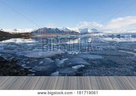 Opeing wooden floor Iceland winter lagoon and mountain clear blue sky background