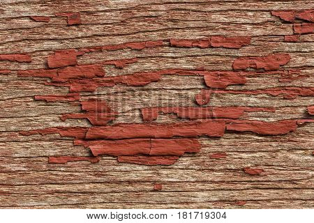 A closeup of red chipped paint on wood siding.