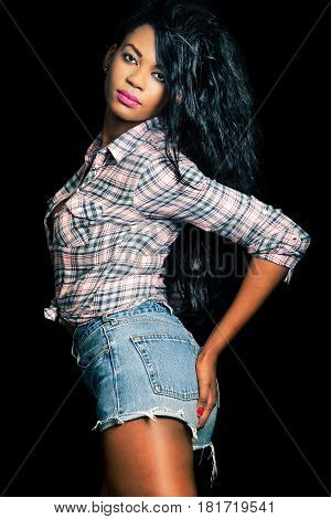Beautiful African American model on a black background. Sexy poses. Provocative attitude with hands on her butt. Shirt and short jeans.