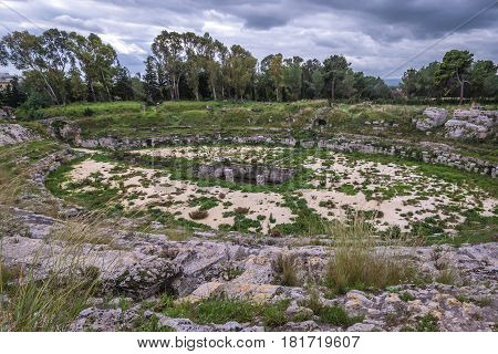 Ruins of amphitheater from Roman period in Neapolis Archaeological Park in Syracuse Sicily Island of Italy