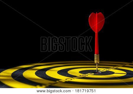 Red Dart Arrow In The Center Of Dartboard. Isolated On Black Background