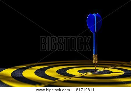 Blue Dart Arrow In The Center Of Dartboard. Isolated On Black Background