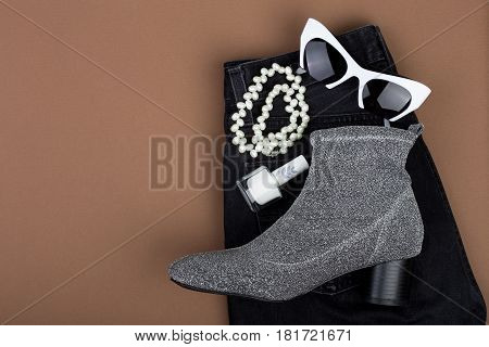 Set Of Woman Stuff On Brown Background: Jeans, Shoe, Sunglasses, Accessories