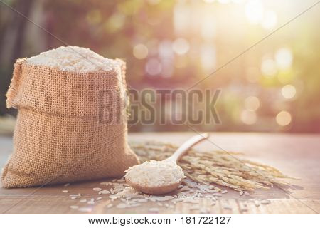 Thai Jasmine Rice In Small Sack On Wooden Table With Sunlight Blur And Bokeh Background In Morning T