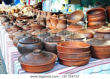 Pottery for sale. Traditional Ceramic Jugs. Handmade Ceramic Pottery in a Roadside Market with Ceramic Pots and Clay Plates Outdoors.