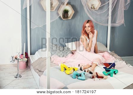 gorgeous young girl with pink hair in a nightgown on the bed full high heels. hesitant, not knowing which pair of shoes to choose for today