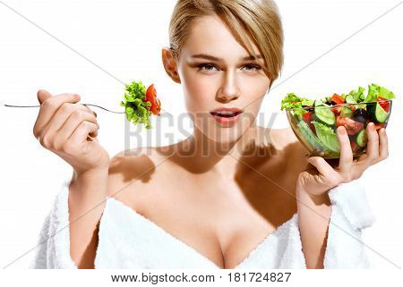 Sexy blonde lady eating healthy food. Photo of beautiful woman in bathrobe isolated on white background. Healthy lifestyle concept