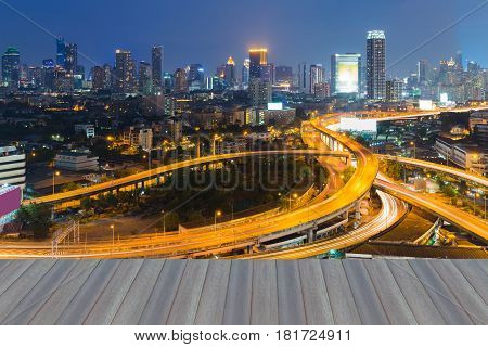 Opeing wooden floor Highway intersection with city downtown background at twilight cityscape background