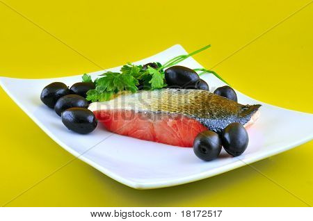 Part of salted fish salmon lying on a white plate beside large black olives poster
