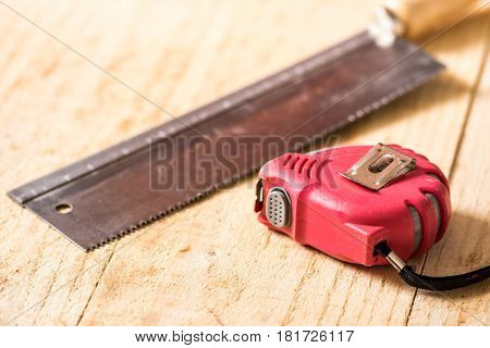 Hand Saw Construction Meter On The Wooden Planks Background