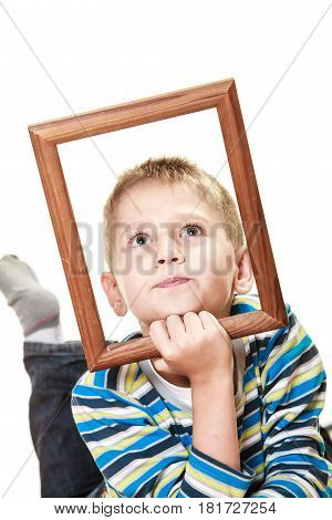 Portrait of little funny blonde boy child holding photo frame framing his face looking up studio shot isolated on white