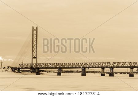 Cable-stayed bridge in winter evening. The biggest bridge in the world with one pylon tower across Ob river in Siberia. Toned.