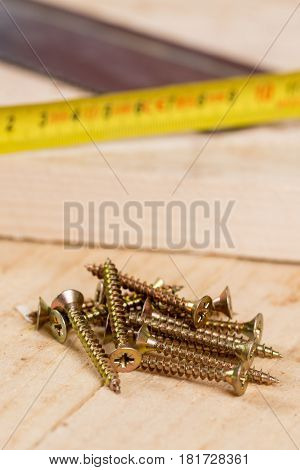 Pile Of Screws With Meter And Hand Saw In Background