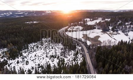 Car driving in a rural area towards the setting sun from a high angle.