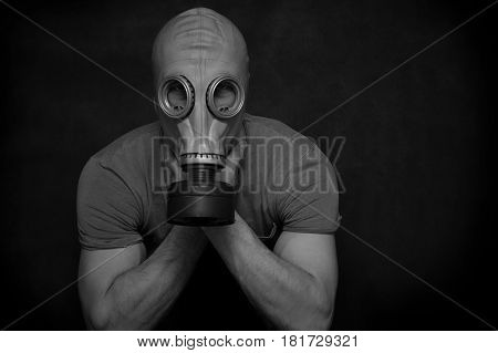 The man in a gas mask on a black background. Conceptual photo, black and white photography