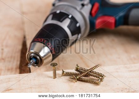 Metal Screw Screwed Into A Wooden Board With Accu Drill