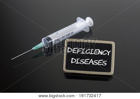 Deficiency Disease on blackboard and syringe. Health concept