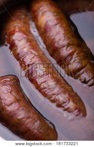 Pieces of traditional Polish pork sausage being steamed.