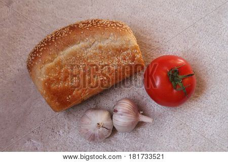 white bread with sesame seeds ripe red tomato and two heads of garlic prepare for made sandwich
