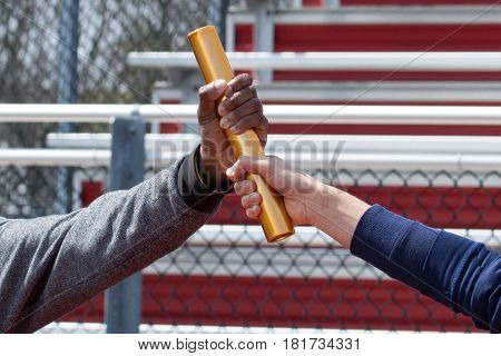 two track athletes exchange a baton while working out at track practice