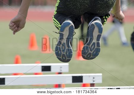 A high school athlete jumping over hurdles for strength work