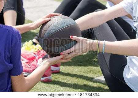 High school girls pass a medicine ball by twisting to the side in a group