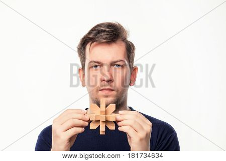 Attractive 25 year old business man looking confused and surprised at camera with wooden puzzle on white studio background.