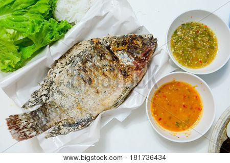 Tilapia fish grilled with Salt and have Spicy Sauce Thai foods style placed