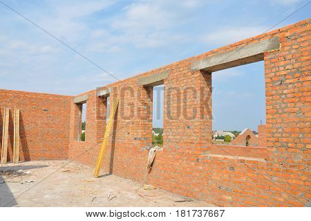 Unfinished Red Brick House Wall under Construction without Roofing. Attic Windows Concrete Lintel Frame Construction. House construction site. Brickwork. unfinished house. poster