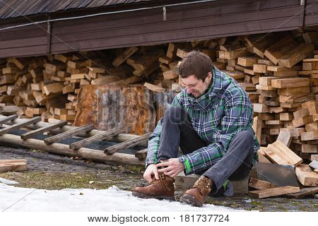 Young man sits near a wall of logs and lace up the shoelaces on his boot.