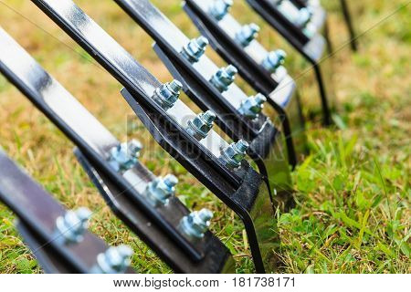 Agriculture industrial equipment concept. Closeup of ripper machinery rods with many screws