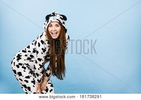 Happy teenage girl in funny nightclothes pajamas cartoon style smiling positive face expression studio shot on blue.