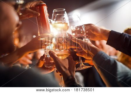 Cheerful friends clinking glasses above dinner table. Alcohol and toasting, party and celebration theme. Congratulations on the event