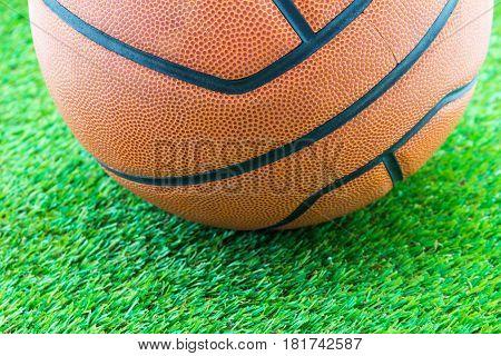 Close up basketball ball on geen grass background
