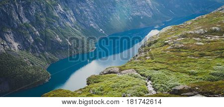 Beautiful norwegian vibrant summer landscape with fjord, mountain and lake, lake Ringedalsvatnet on the way to famous Trolltunga, Skjegeddal rock, near Odda, Hordaland, Norway.