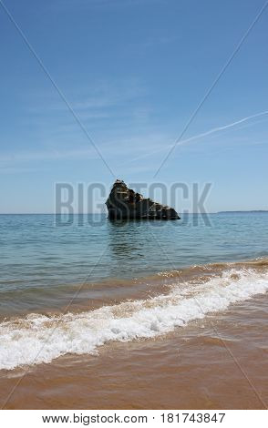 Portugal Algarve Portimao. lonely rock and wave in atlantic ocean on the blue sky background vertical view