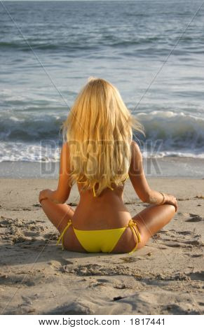 Young Woman Meditating On The Beach.