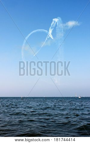 White heart drown by airplane and sea on the blue sky background vertical view