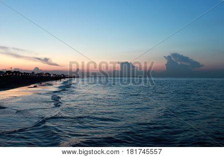 Italy. Emilia-Romagna. Rimini. Sunset on sea on blue pink sky background horizontal view