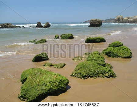 Portugal Algarve Portimao. Green stones on the beach on atlantic ocean and blue sky background horizontal view